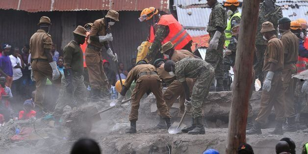 Rescue workers remove debris from the rubble of the six-storey building that collapsed killing 23 people...