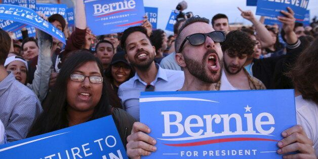 Members of a crowd cheer as they listen to Democratic U.S. presidential candidate Bernie Sanders speak...