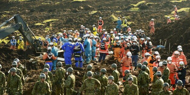 Rescue workers and Japan Ground Self-Defense Force soldiers conduct search and rescue operations at site...