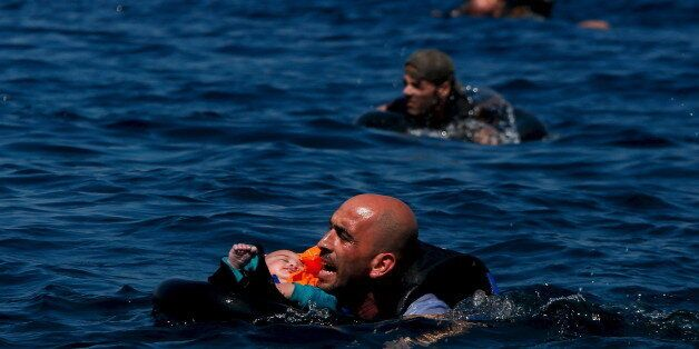 A Syrian refugee holding a baby swims towards the Greek island of Lesbos, September 12, 2015. Alkis Konstantinidis:...