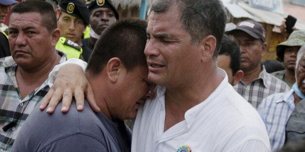 Ecuador's President Rafael Correa (R) embraces a resident after the earthquake, which struck off the...