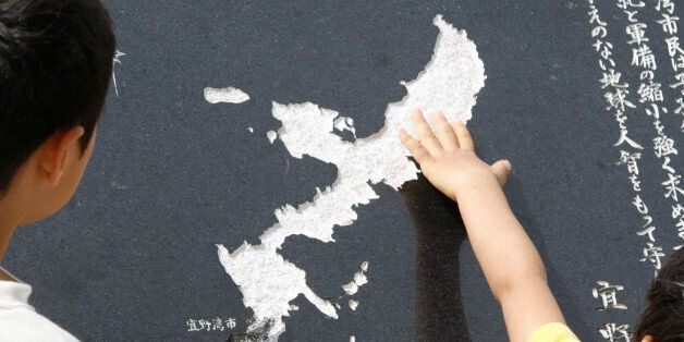 A Okinawa boy touches the map of Okinawa carved on a stone face near the U.S. Marine Corps Air Station...