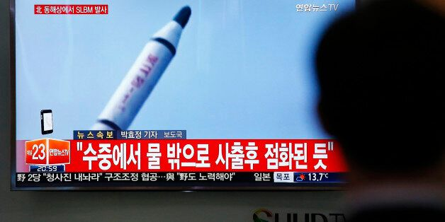 A man watches a TV news program showing a file footage of a missile launch conducted by North Korea,...
