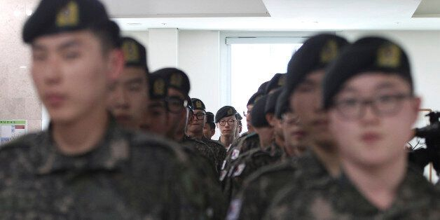 South Korean army soldiers wait to cast their preliminary votes for the upcoming parliamentary election...