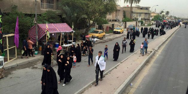 Shiite pilgrims march toward the Imam Mousa al-Kadhim shrine to commemorate the anniversary of the Imam's...