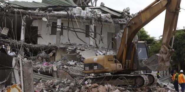 An excavator clears debris from a collapsed building in Portoviejo, after an earthquake struck off Ecuador's...