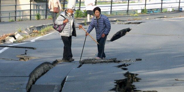 Local residents look at cracks caused by an earthquake on a road in Mashiki town, Kumamoto prefecture,...