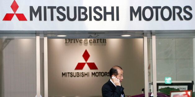 A man talking on the mobile phone walks out from the headquarters of Mitsubishi Motors Corp. in Tokyo...