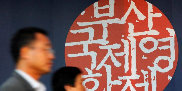 People walk past a logo of the 15th Pusan International Film Festival before the opening ceremony of...