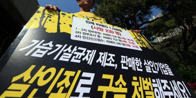 19일 오후 서울 서초동 서울중앙지검 앞에서 가습기 살균제 피해자 가족이 살균제 업체 관계자들의 강력한 처벌을 요구하며 팻말을 든 채 1인 시위를 하고