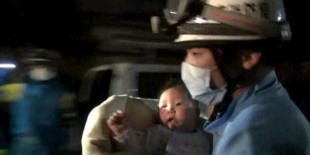 An eight-month-old baby is carried away by a rescue worker after being rescued from her collapsed home...