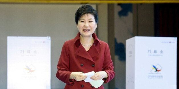 South Korean President Park Geun-hye casts her ballot at a polling station in Seoul, in this handout...