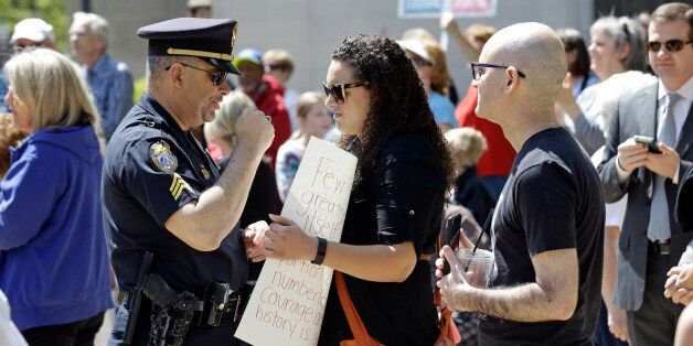 A police officer confronts a lady holding a sign at the North Carolina State Capitol in Raleigh, N.C.,...