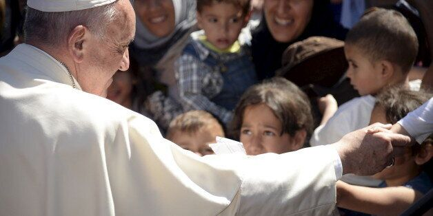 Pope Francis greets migrants and refugees at the Moria refugee camp near the port of Mytilene, on the...