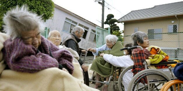 Evacuees from a nursing home wrap themselves in blankets as they take shelter outside their damaged nursing...