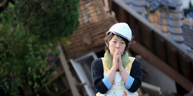 A woman reacts in front of collapsed house caused by an earthquake in Mashiki town, Kumamoto prefecture,...