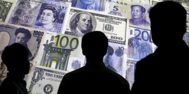 People are silhouetted against a backdrop projected with the picture of various currencies of money in...
