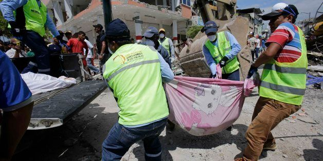 Volunteers carry a body pulled from the rubble in Pedernales, Ecuador, Sunday, April 17, 2016. Rescuers...