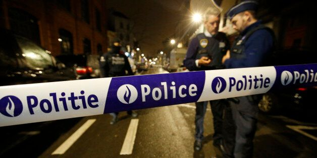 Police guard a check point during a police raid in the suburb of Schaerbeek in Brussels, Thursday, March,...