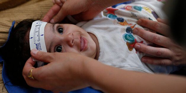 Three-month-old Esther Kamilly has her head measured by Brazilian and U.S. health workers from the United...