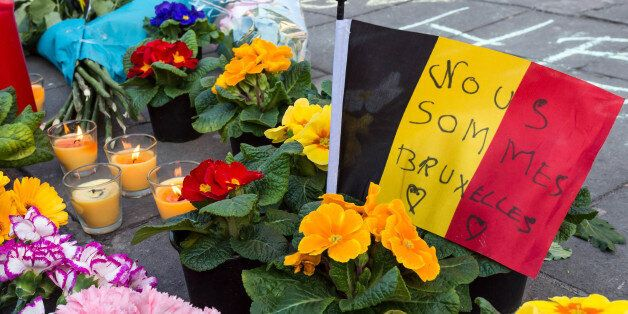 A memorial to attack victims with a Belgian flag and flowers is set up outside the stock exchange in...