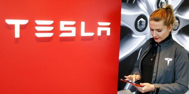 A Tesla employee stands beside a company logo in the dealership in Berlin, Germany, November 18, 2015....