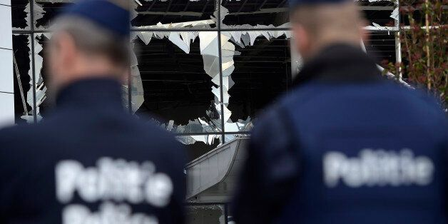 Two police officers stand in front of blown out windows at Zaventem Airport in Brussels on Wednesday,...