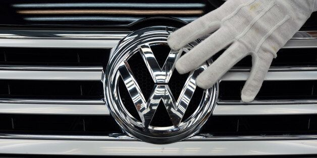 FILE - In this Oct. 23, 2015 file photo a worker touches the logo of Volkswagen AG on a Phaeton in Dresden,...