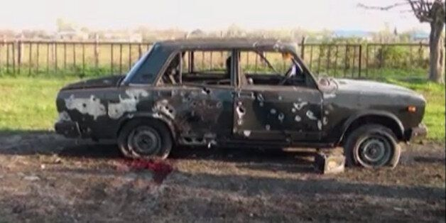 In this image from TV, a car destroyed with blood showing in the aftermath after heavy fighting erupted...