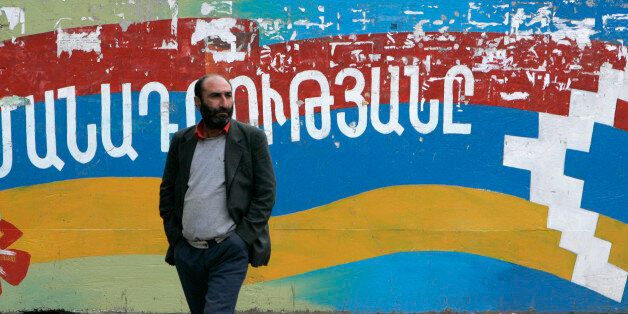 A man stands near a wall decorated with national flag of Nagorno Karabakh in Stepanakert October 28,...
