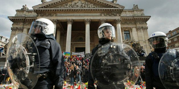 Police in riot gear protect one of the memorials to the victims of the recent Brussels attacks, a right...