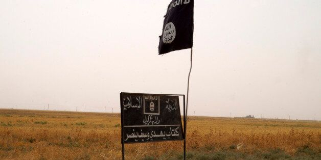 Islamic State group's flag is seen in an area after Kurdish troops known as peshmerga regained control...