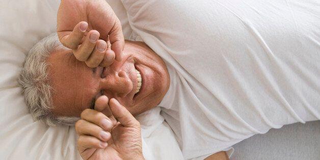 portrait of mature man awaking rubbing his