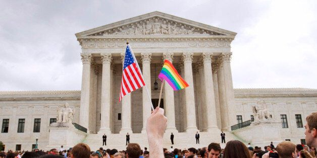 FILE - In this June 26, 2015 file photo, a man holds a U.S. and a rainbow flag outside the Supreme Court...