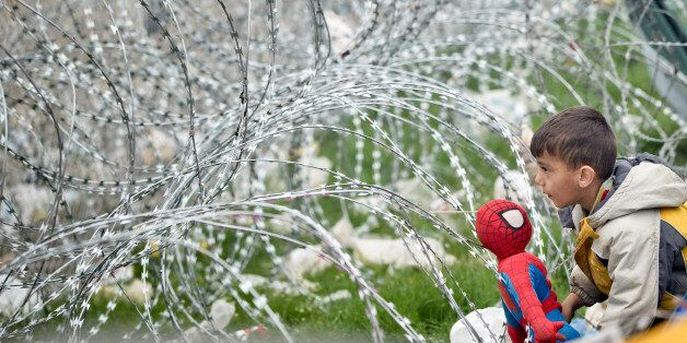 A boy plays with a Spiderman doll next to the razor wire around the fence between Greece and Macedonia...