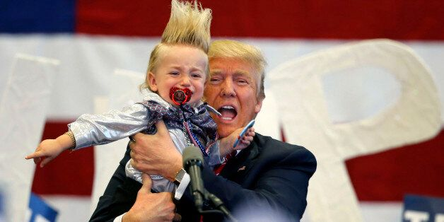 Republican presidential candidate Donald Trump holds up a child he pulled from the crowd as he arrives...