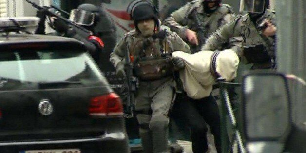 In this framegrab taken from VTM, armed police officers escort a suspect to a police vehicle during a...