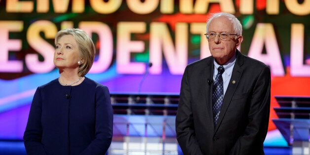 Democratic presidential candidates Hillary Clinton, left, and Sen. Bernie Sanders, I-Vt., stand on stage...