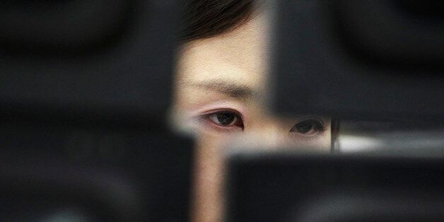 FILE - In this Tuesday, Feb. 4, 2014, file photo, a currency trader watches monitors at the Korea Exchange...