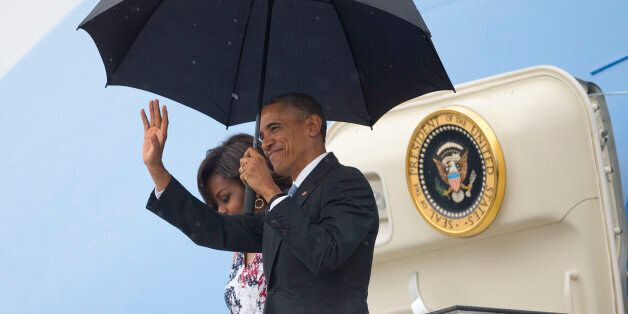 President Barack Obama, right, arrives with first lady Michelle Obama as they exit Air Force One at the...