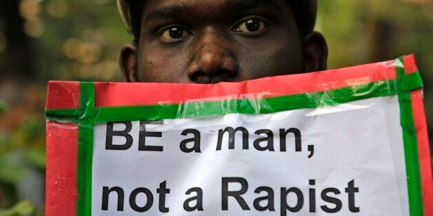 A man holds a placard as Indian Christians and others condemn the gang rape of a nun at a Christian missionary...