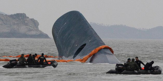 FILE - In this April 17, 2014 file photo, South Korean Coast Guard personnel search for missing passengers...