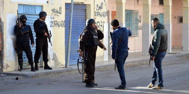 Tunisian police officers take positions during clashes with militants in Ben Guerdane, 650 km away from...