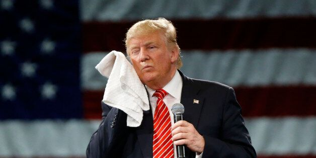 Republican presidential candidate Donald Trump wipes his cheek as he listens to a question from an audience...