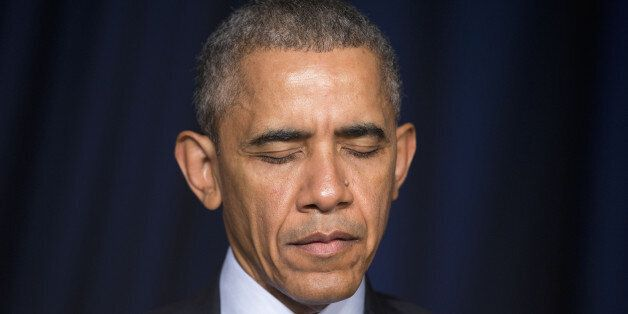 President Barack Obama closes his eyes while a prayer is said during the National Prayer Breakfast in...