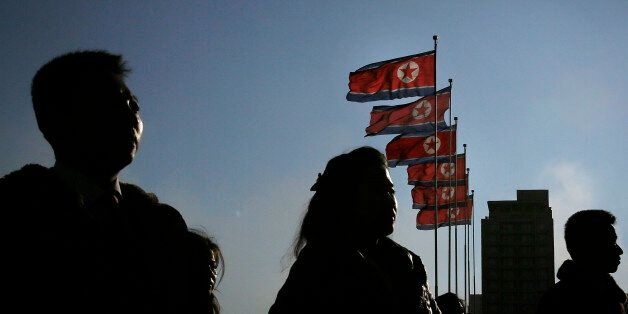 North Korean men and women are silhouetted with their country's national flags in the background during...