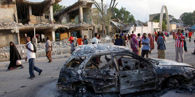 Somalis walk near destroyed buildings and the wreckage of a car, Saturday, Feb. 27, 2016 after a suicide...