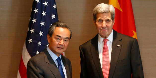 US Secretary of State John Kerry, right, shakes hands with China's Froreign, Minister Wang Yi, during...