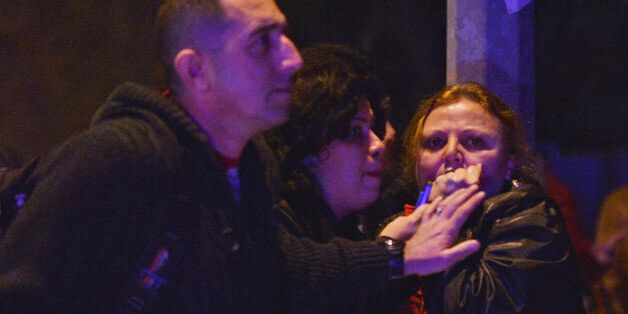 People react at the scene of an explosion in Ankara, Wednesday, Feb. 17, 2016. A large explosion, believed...