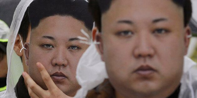 North Korean defectors wearing masks of North Korean leader Kim Jong Un attend a rally against North...